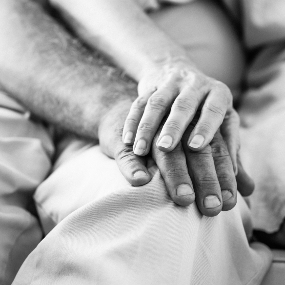 @Glowimages: Senior couple holding hands at home in the living room